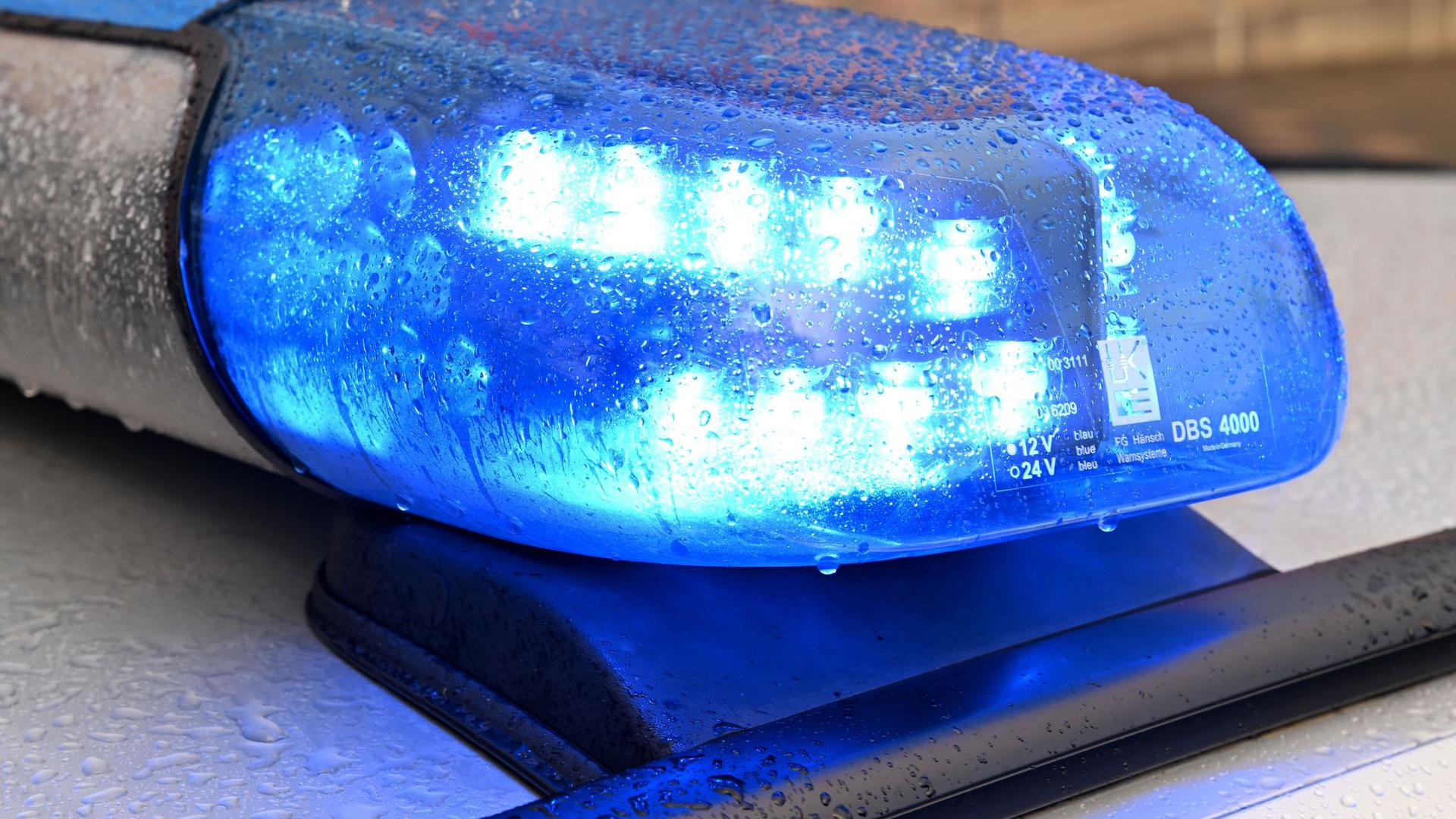 Ein Streifenwagen der Polizei steht mit eingeschaltetem Blaulicht an einem Einsatzort.