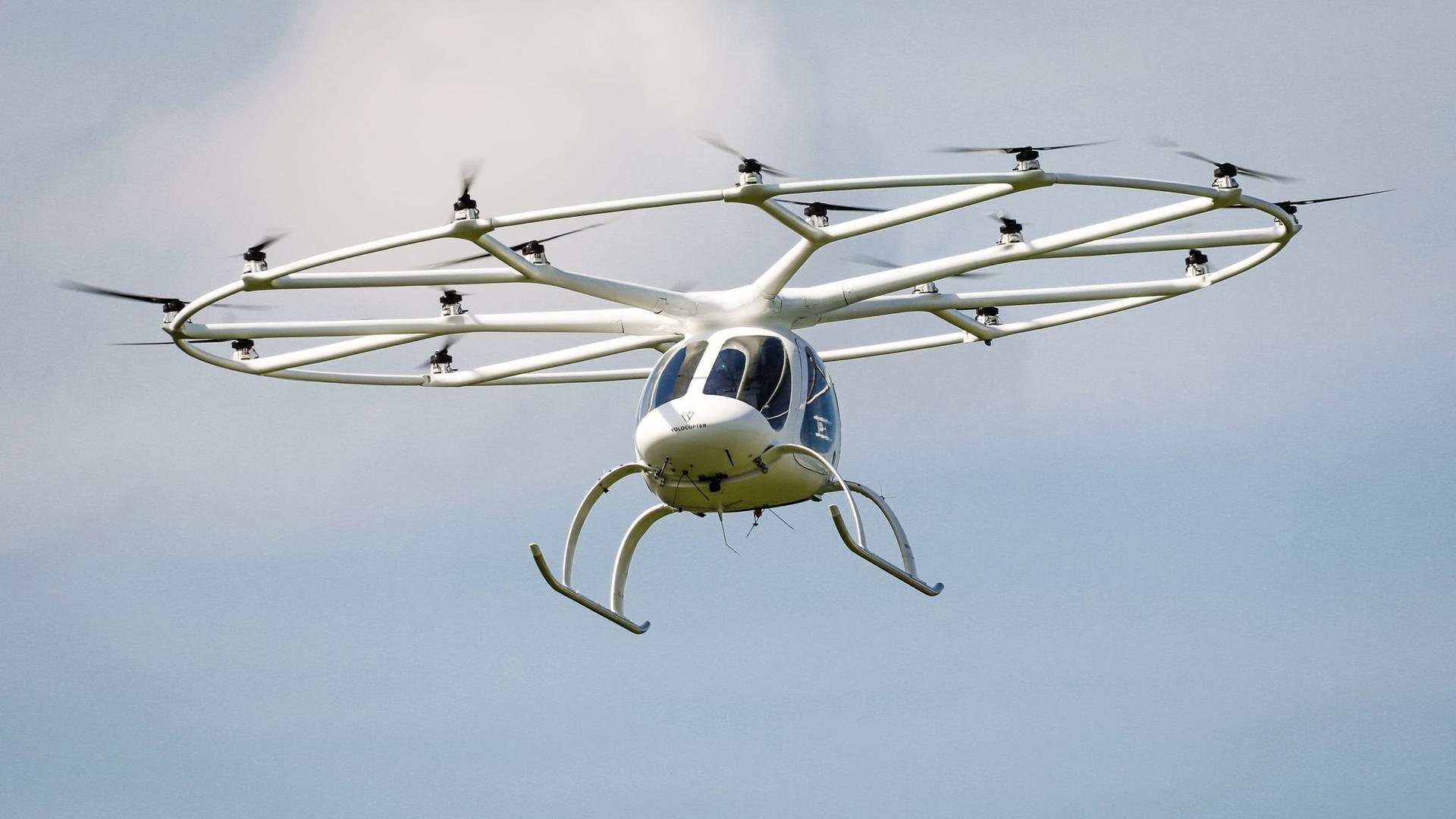 Ein Volocopter fliegt in einer europäischen Innenstadt.