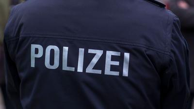 """""""Polizei"""" steht auf der Uniform eines Polizisten."""