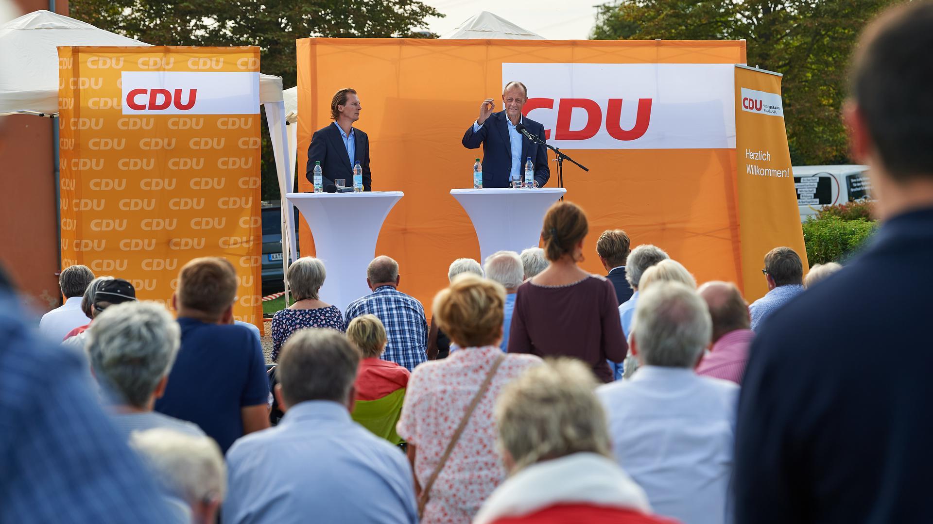 Zwei Männer auf einem Podium, dahinter Wahlwerbung der CDU.