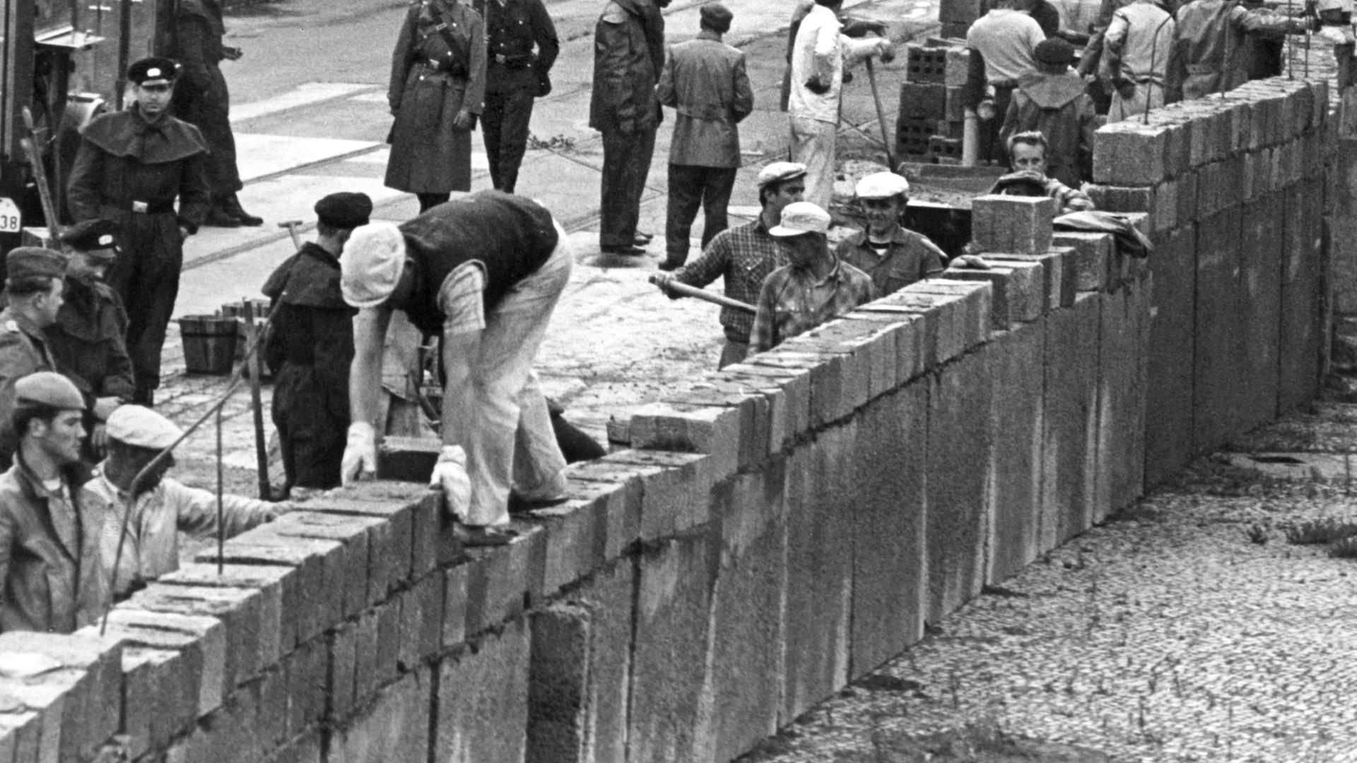 Unter der Aufsicht von bewaffneten Volkspolizisten errichtet eine Ostberliner Maurerkolonne am an der sowjetisch-amerikanischen Sektorengenze am Potsdamer Platz eine Mauer.
