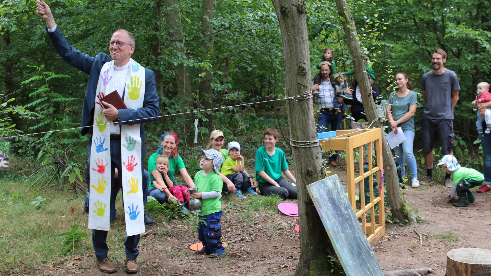 Als jüngster Ministrant von Pfarrer Peter Bretl fungierte bei der Einweihung des Waldkindergartens der dreijährige Leon. Kniend im Hintergrund die Erzieherinnen Nora Leipner, Beatrice Schuster und Sina-Fee Zacher (v.l.)