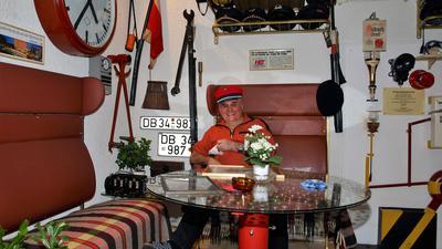 Ein Mann sitzt auf einer Zugbank. Über ihm ist eine Gepäckablage, an den Wänden hängen verschiedene Exponate: Schilder, eine Fagnem Mützen, eine Uhr und weiteres. Vor der Zugbank steht ein Tisch, der aus dem Rad einer Dampflok gebaut wurde.