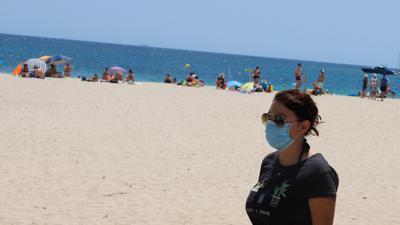 Eine junge Frau mit einer Schutzmaske an einem Strand.