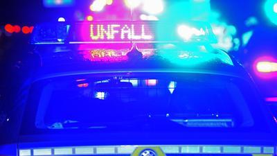 """Blaulicht und der LED-Schriftzug """"Unfall"""" auf dem Dach eines Polizeistreifenwagens."""
