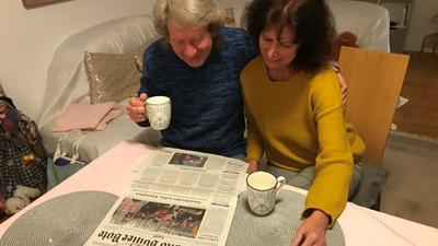 Zwei Personen lesen Zeitung am Tisch