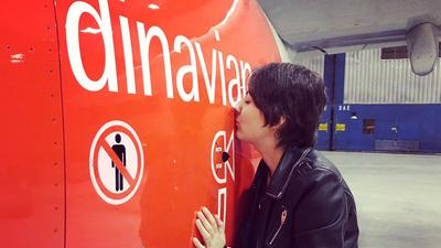Michèle steht in einem Hangar und küsst ein Flugzeug.