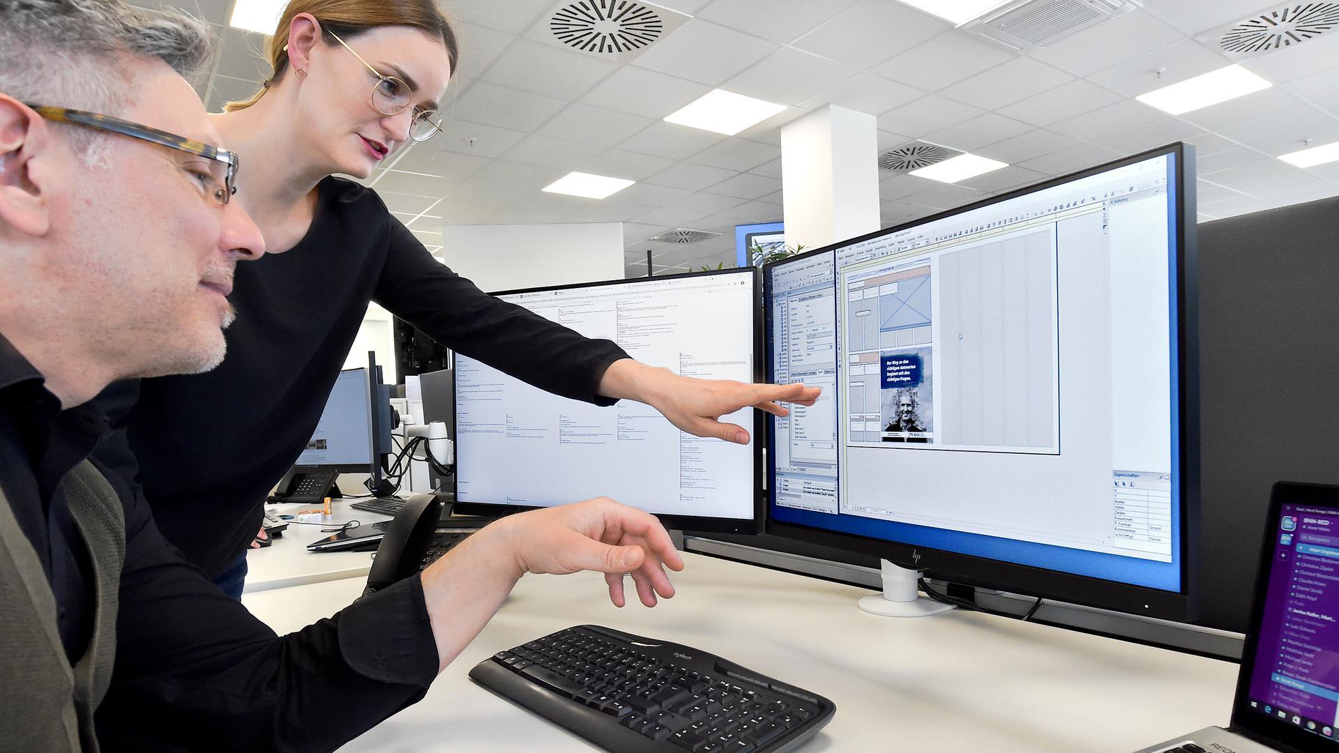 Zwei Menschen schauen auf einen Computer.