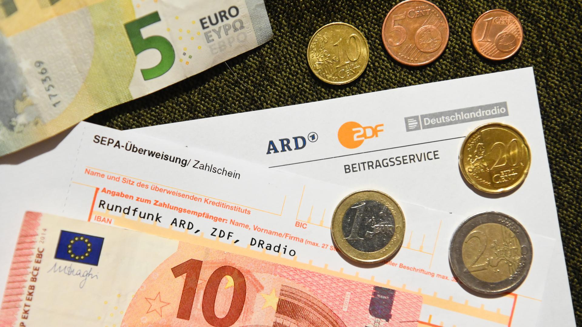 """Auf einem Tisch liegt ein Anschreiben und Überweisungsträger für die Rundfunkgebühren, sowie der Betrag von 18 Euro und 36 Cent. (zu dpa """"Corona-Folgen für Rundfunkbeitrag noch unklar"""") +++ dpa-Bildfunk +++"""