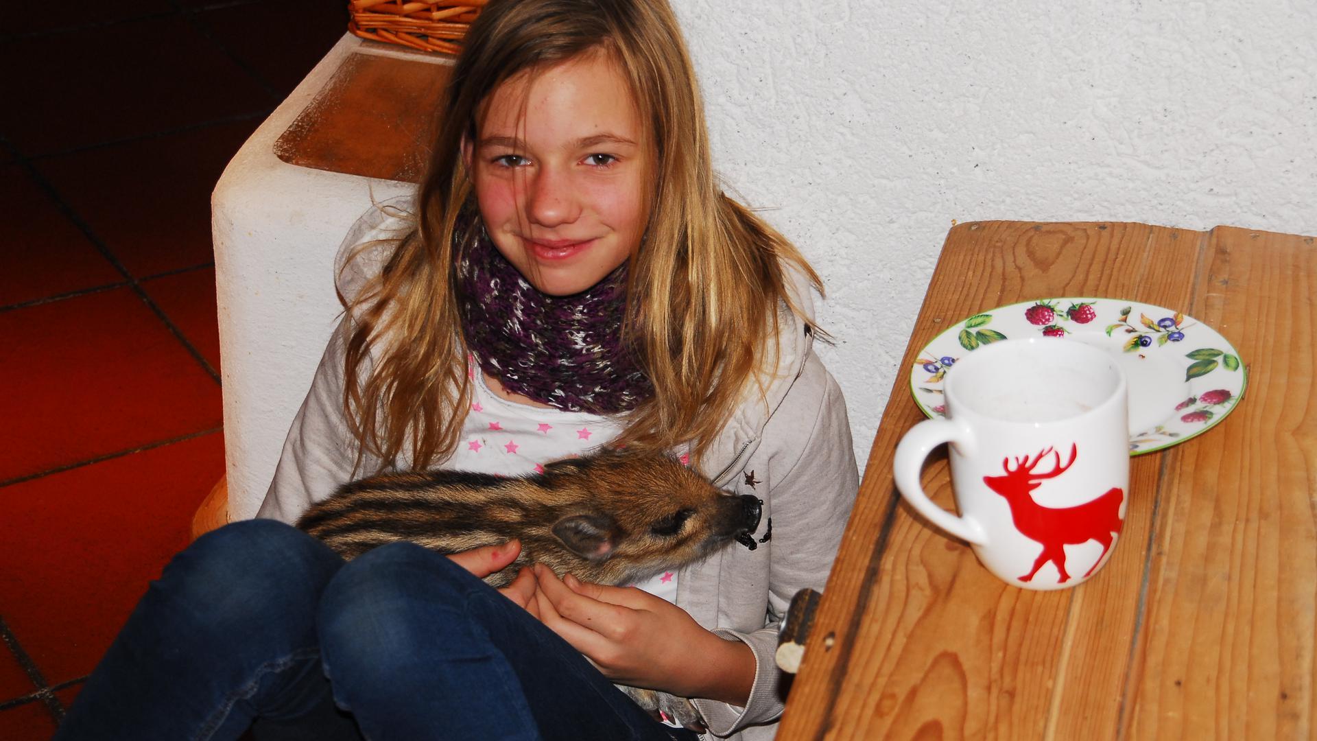 Das Wildschwein-Baby im Schoß von Lisa Carstensen