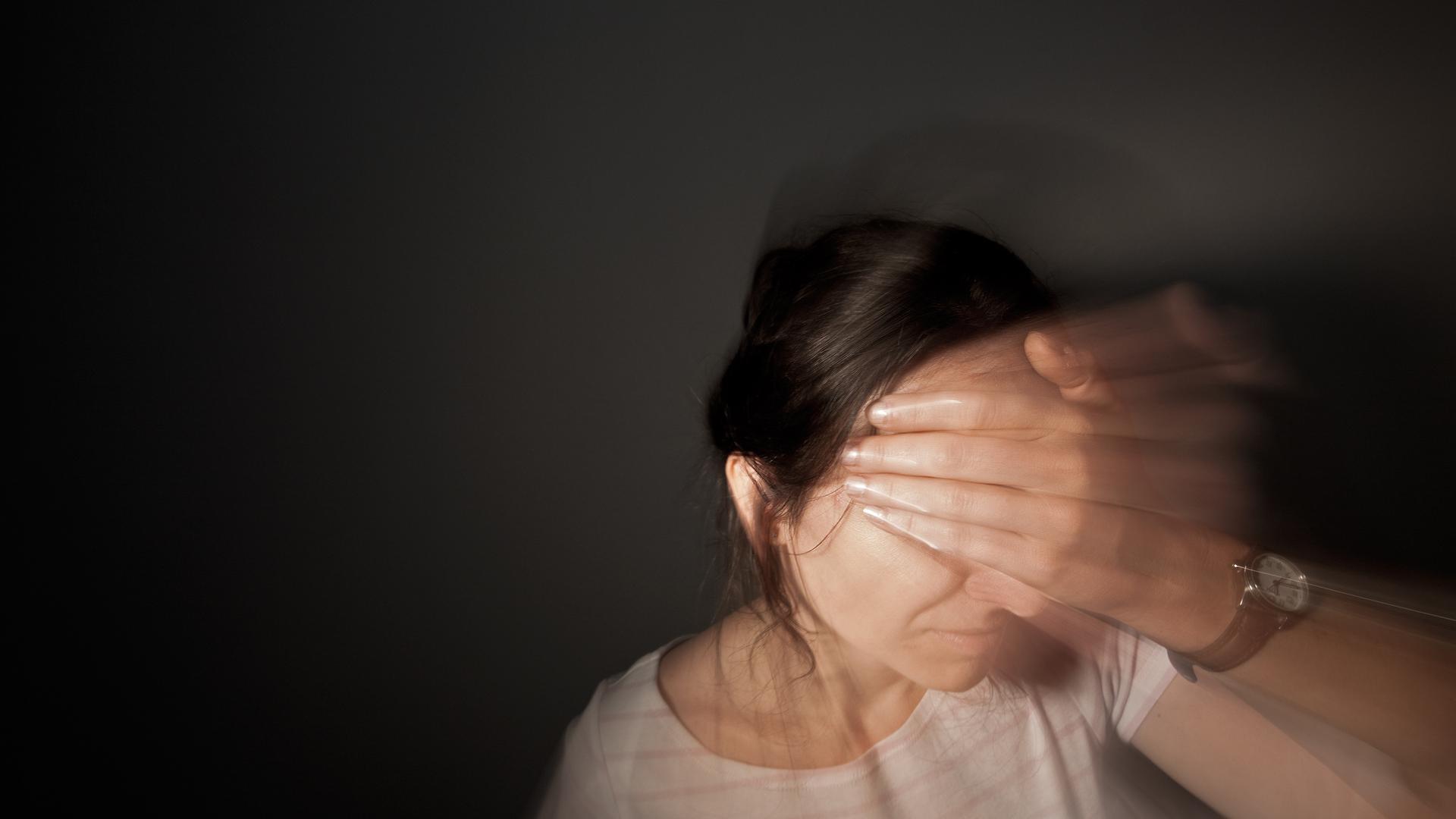 Eine Frau fasst sich an den Kopf.
