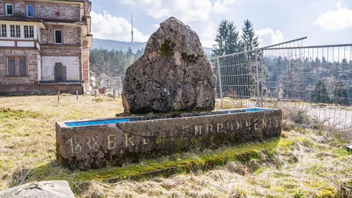 Ein Stein steht vor der Klinik Breitenbrunnen hinter einem Bauzaun.