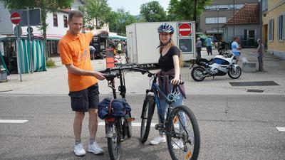 Ein Mann und ein Mädchen stehen mit ihrem Fahrrad auf einer Kreuzung.