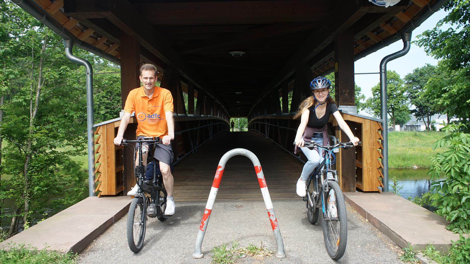 Ein Mann und eine junge Frau fahren über eine Brücke.