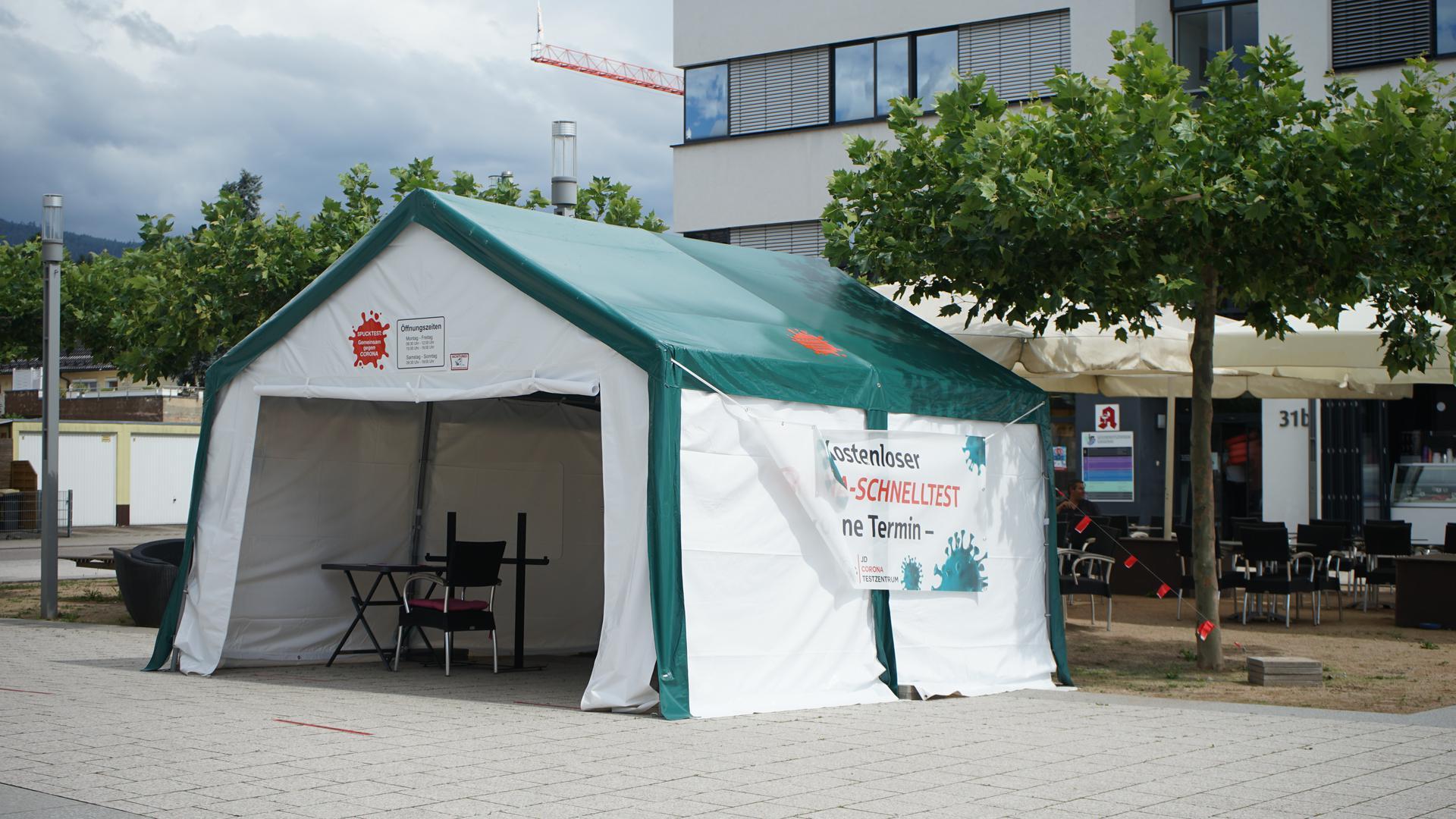 Ein Zelt steht auf einem Platz vor einem großen Gebäude.