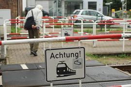 Ein Mann läuft über einen Bahnübergang.