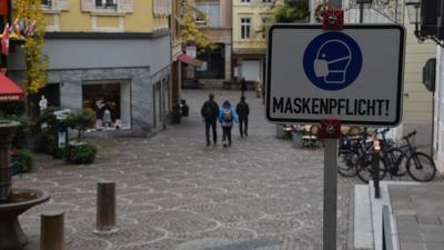 Ein Schild weist auf die Maskenpflicht in der Baden-Badener Innenstadt hin.