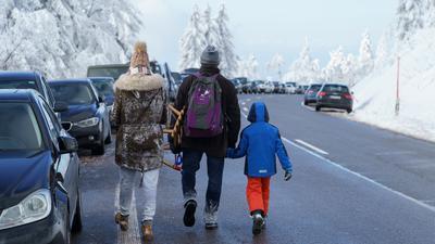 Eine Familie läuft zu ihrem Auto das an der Schwarzwaldhochstrasse geparkt ist.