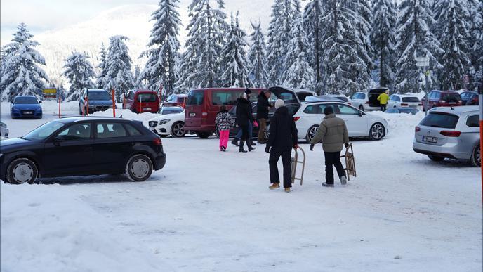 Winter-Ausflügler mit ihren Schlitten laufen zu geparkten Fahrzeugen am Ruhestein.