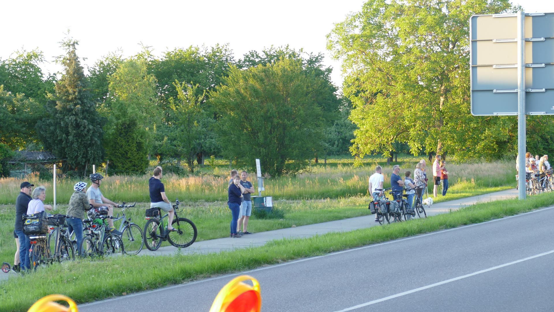 Einige Radfahrer stehen auf einem Weg.