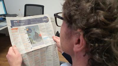Ein Mann schaut sich das Programm der VHS Baden-Baden an.