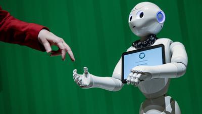Ein Roboter interagiert mit einer Frau auf einer Veranstaltung, die eine Auswahl hoch entwickelter Roboter aus verschiedenen Bereichen zeigt, die einen Einblick in die aktuellen Möglichkeiten der Künstlichen Intelligenz gibt.