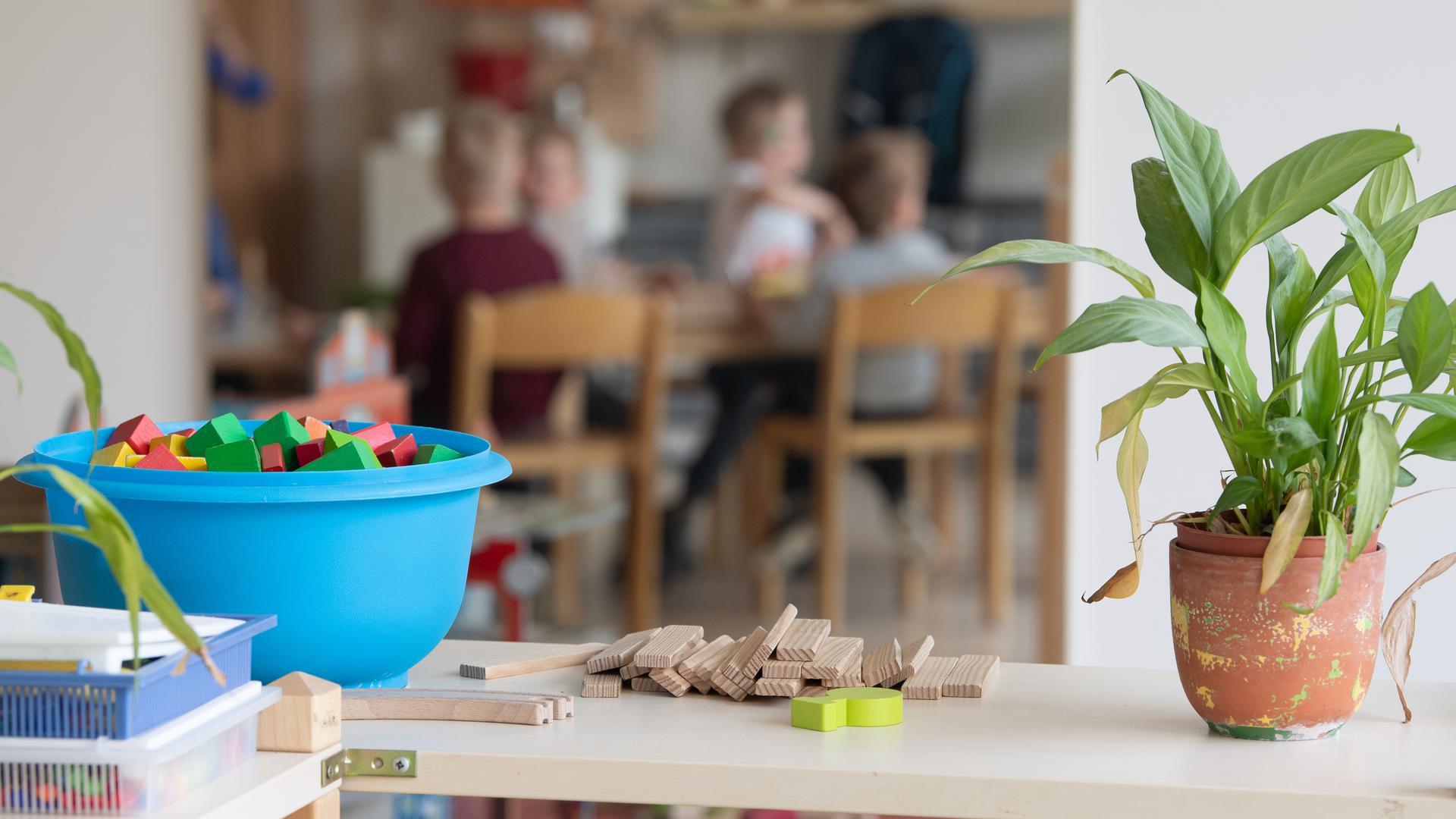 Kinder sitzen im Rahmen der Notbetreuung in einem Kindergarten während des Mittagessens an einem Tisch und sind in einem Spiegel zu sehen.