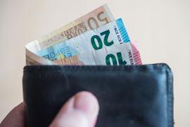 Geldscheine im Wert von fünf, zehn, zwanzig, fünfzig und hundert Euro stecken in einem Geldbeutel, der von einer Hand gehalten wird.