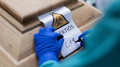 Christoph Kuckelkorn, Bestattungsunternehmer schreibt «C19» auf ein Schild mit dem Hinweis «Infektiös» auf einen Sarg mit einem Verstorbenen, der an oder mit dem Coronavirus gestorben ist. +++ dpa-Bildfunk +++