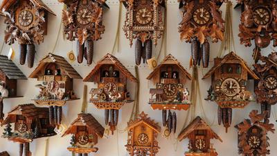 Kuckucksuhren hängen an einer Wand  in einer  Uhrenmanufaktur