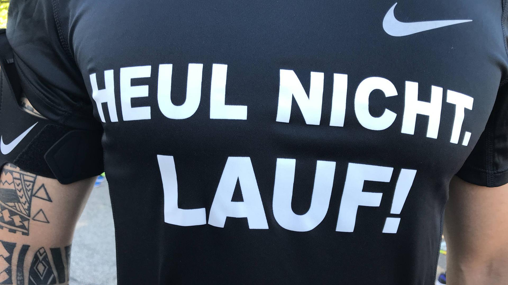 """Ein Teilnehmer beim Heel-Lauf am 28. Juni 2019 in Baden-Baden trägt ein Shirt mit der Aufschrift: """"Heul nicht, lauf!"""""""