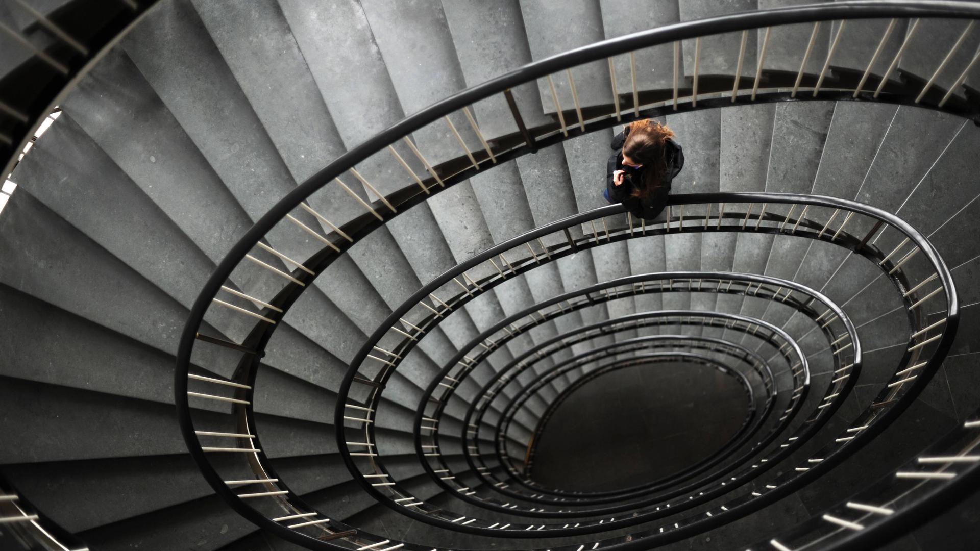 Eine Frau geht eine lange, im Kreis gewundene Treppe hinunter.