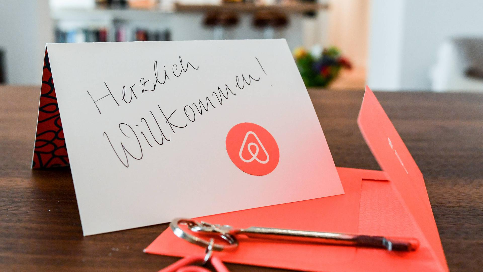 ARCHIV - ILLUSTRATION - 16.04.2018, Berlin: Ein Schlüssel mit einem Airbnb-Anhäger und eine Herzlich-Willkommen-Karte liegen in der Wohnung eines Airbnb-Gastgebers (Gestellte Aufnahme). Die Internetplattform verstoße mit teils unklaren Preisangaben und unzulässigen Geschäftsbedingungen gegen EU-Recht und habe bis Ende August Zeit für Korrekturen, erklärte die Brüsseler Behörde am 16.07.2018 gemeinsam mit europäischen Verbraucherschutzbehörden. (zu dpa «EU-Kommission mahnt Airbnb wegen Regelverstößen ab» vom 16.07.2018) Foto: Jens Kalaene/dpa-Zentralbild/dpa +++ dpa-Bildfunk +++   Verwendung weltweit