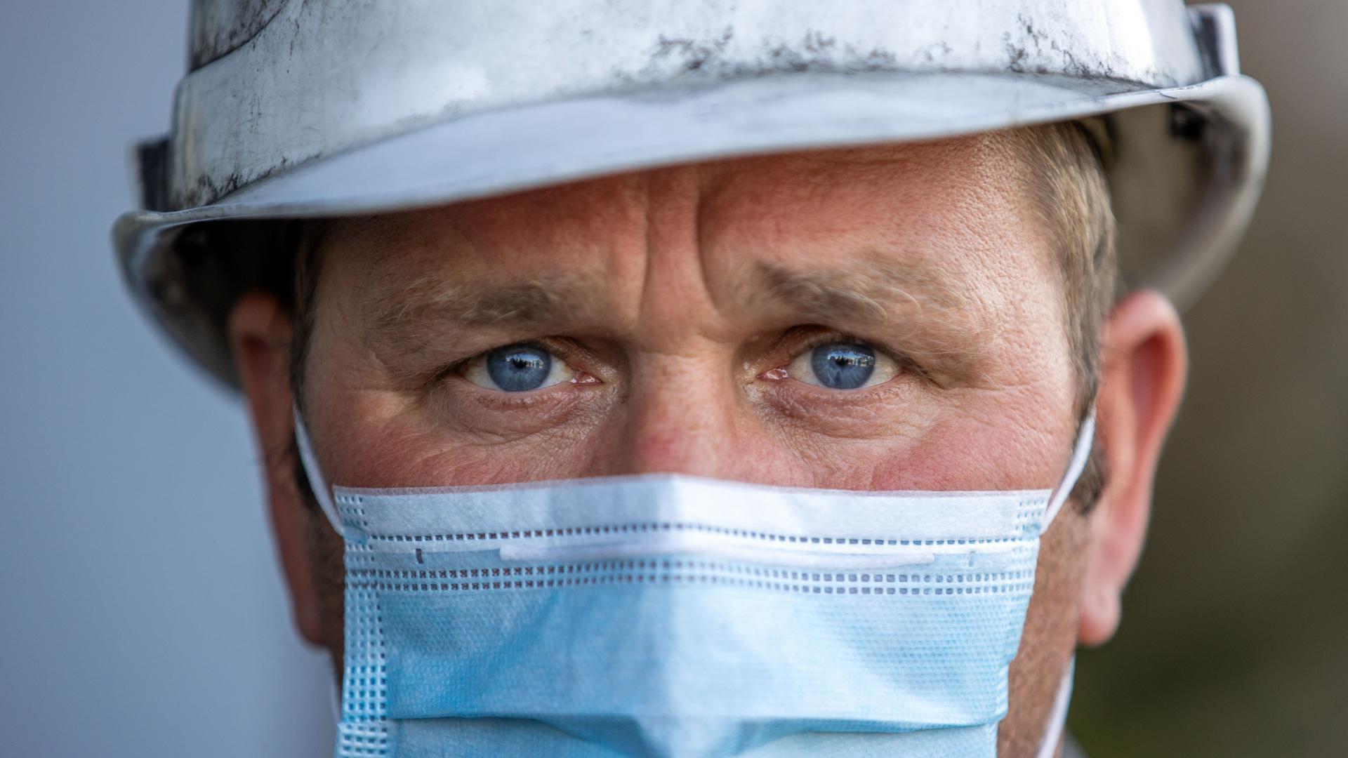 Ein Arbeitnehmer, der in der Corona-Krise eine Mund-Nasen-Schutzmaske trägt, blickt sorgenvoll in die Zukunft.