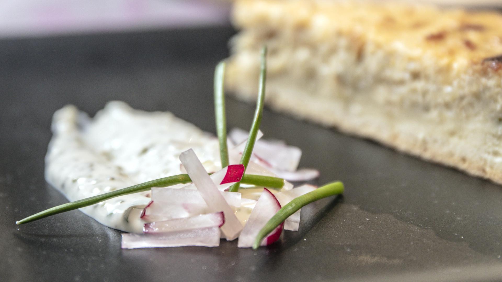 Ein Stück Quiche mit dazugehörigem Dip liegt auf einem Teller.