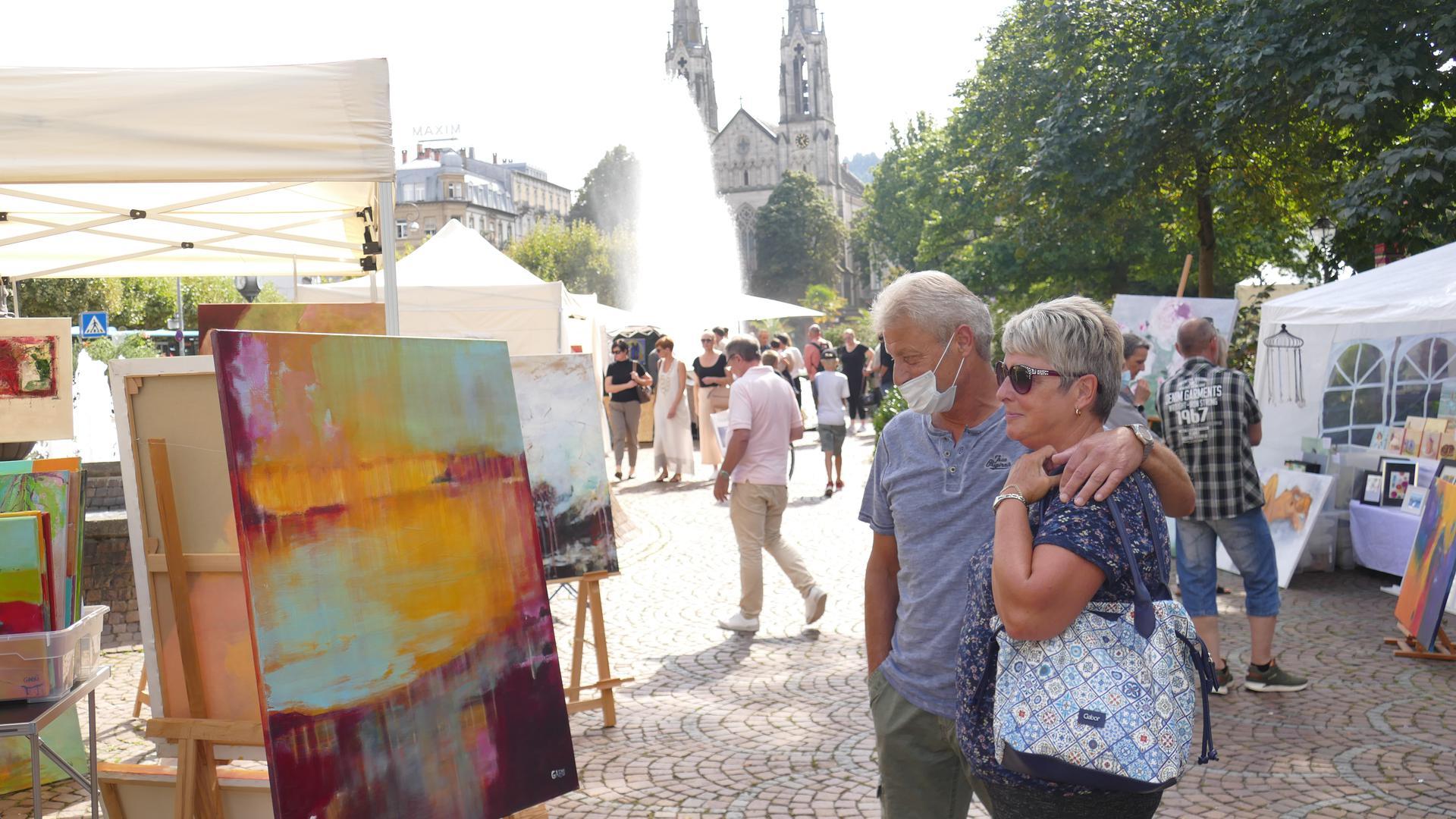 Besucher auf dem Kunstmarkt in Baden-Baden auf dem Augustaplatz betrachten ein Gemälde.