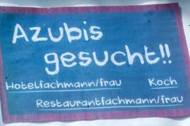 """Ein selbstgemaltes """"Azubis-Gesucht""""-Schild hängt vor einem Hotel."""
