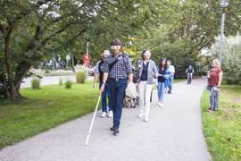Eine Gruppe von Menschen läuft in Baden-Baden über einen Fußgängerweg. Sie haben einen Blindenstock in der Hand und tragen spezielle Brillen.