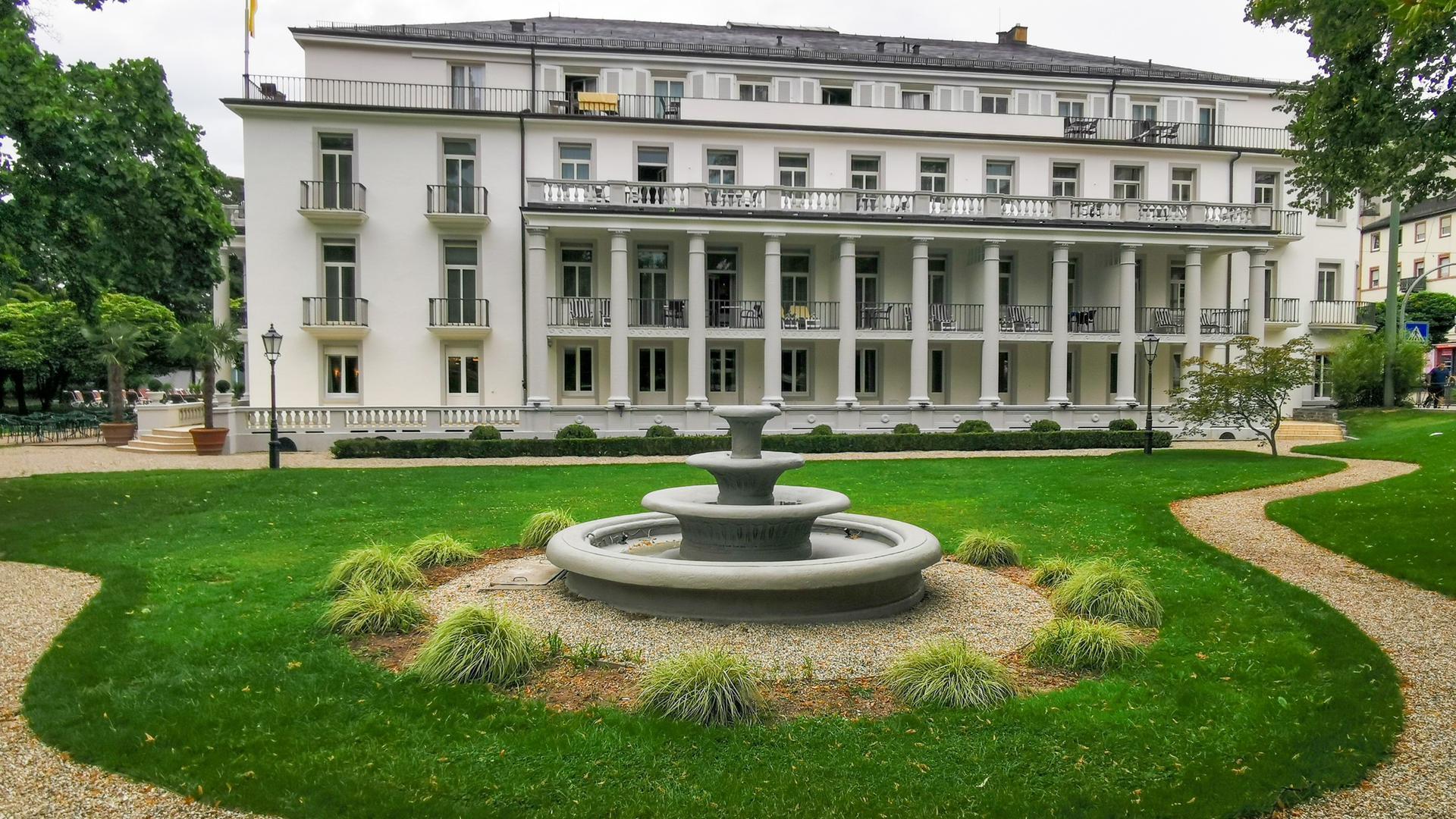 Im Garten des Hotels Badischer Hof steht ein historischer Brunnen.