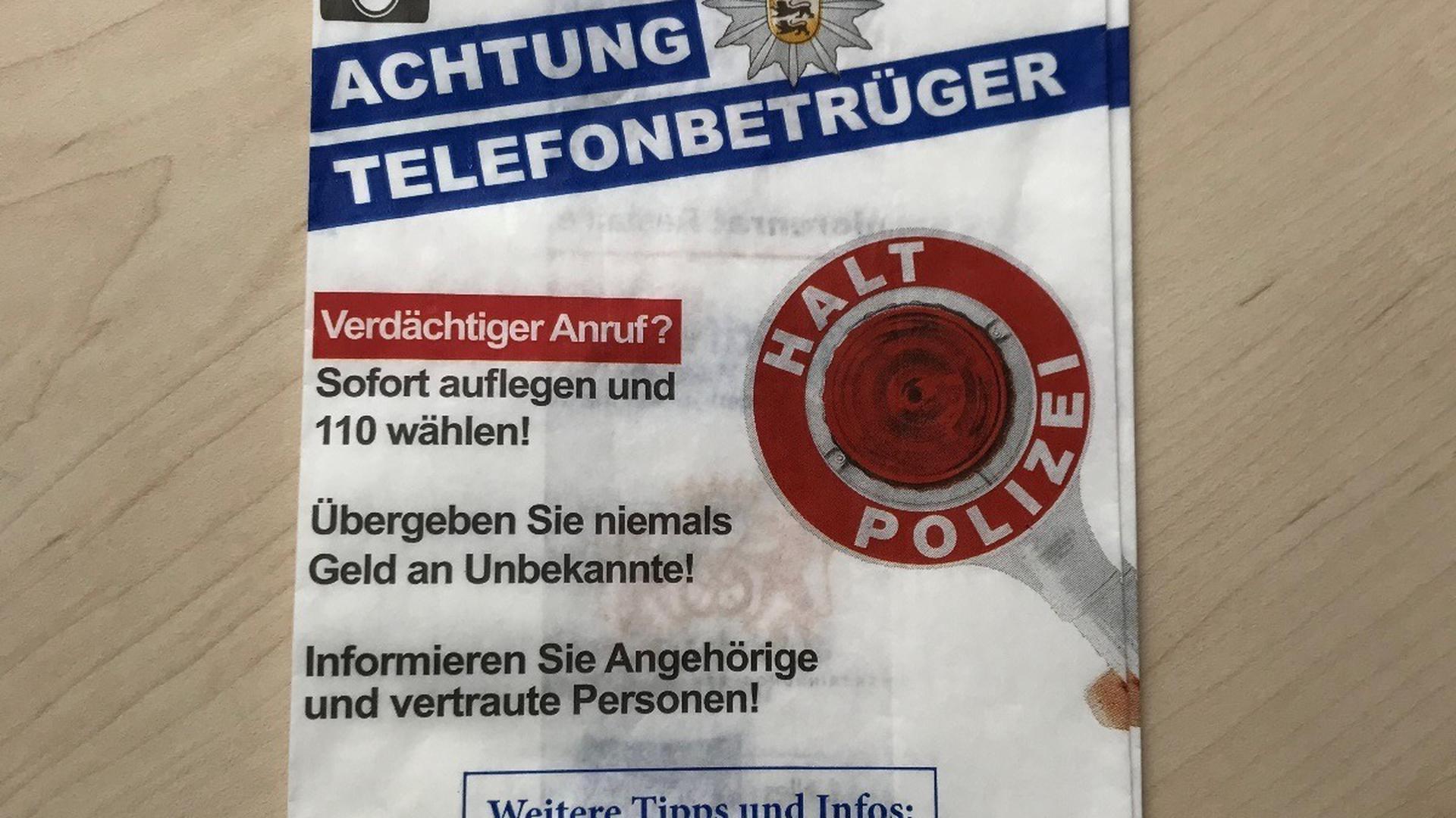 Auf einem Tisch liegt eine Bäckertüte. Sie ist mit Warnhinweisen der Polizei bedruckt. Gewarnt wird vor Telefonbetrügern.