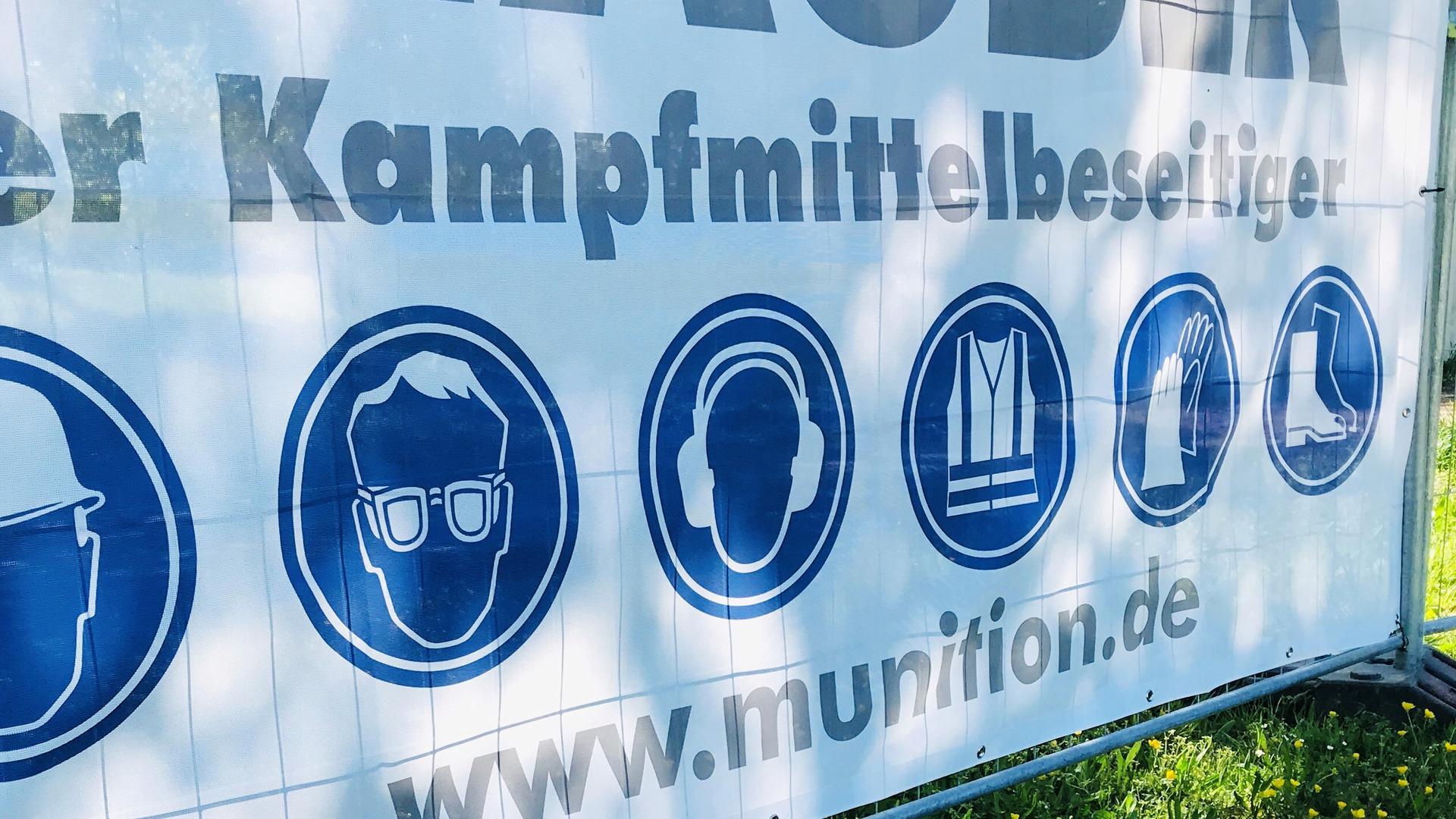 """Ein Transparent mit der Aufschrift """"Der Kampfmittelbeseitiger"""" hängt an einem Zaun im Wörthböschelpark in Baden-Baden."""