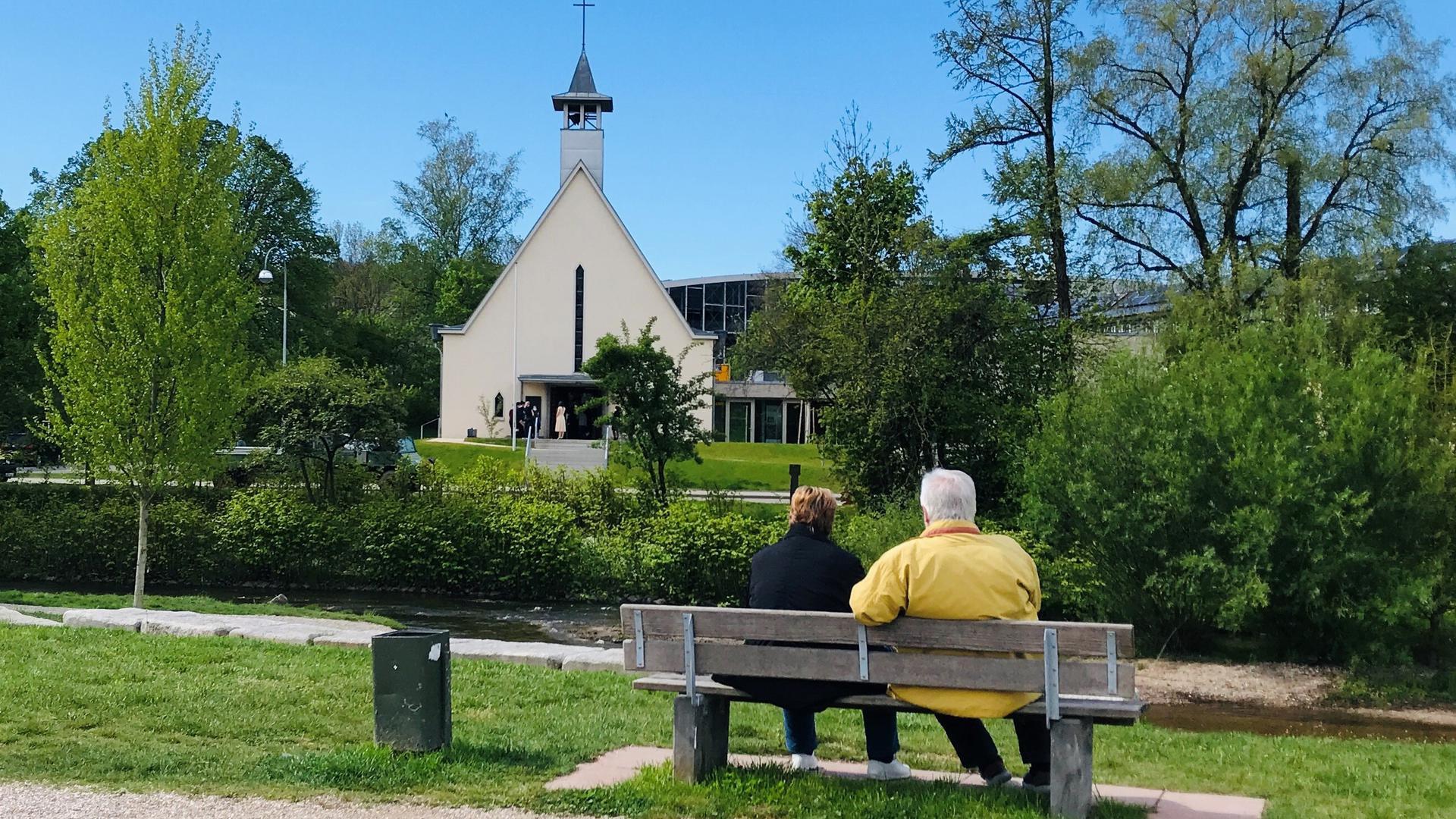 Ein Paar sitzt auf einer Bank im Wörthböschelpark in Baden-Baden - mit Blick auf die Oos und die Friedenskirche.
