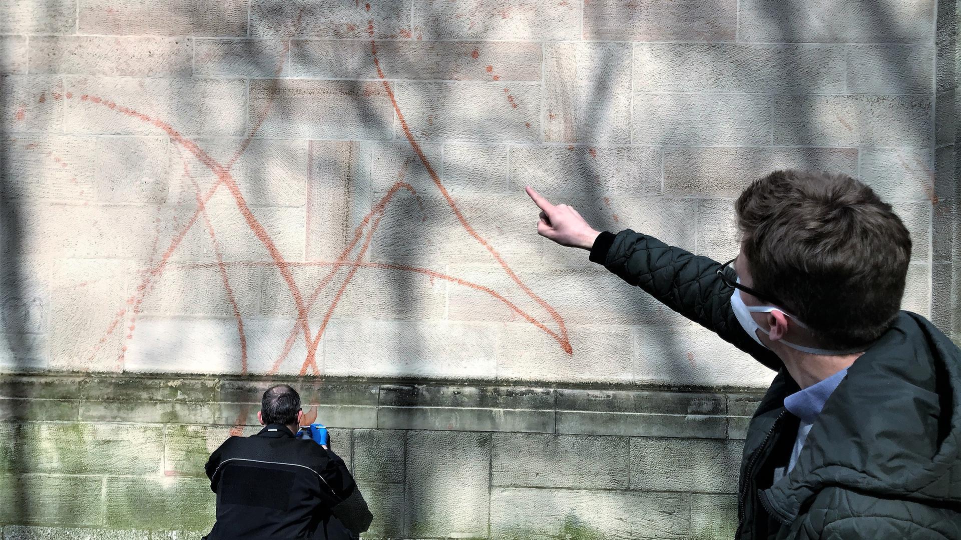 Ein Mann zeigt auf die Fassade der Kirche St. Bernhard in Baden-Baden, auf die Unbekannte ein Zeichen wie einen Davidstern geschmiert haben.