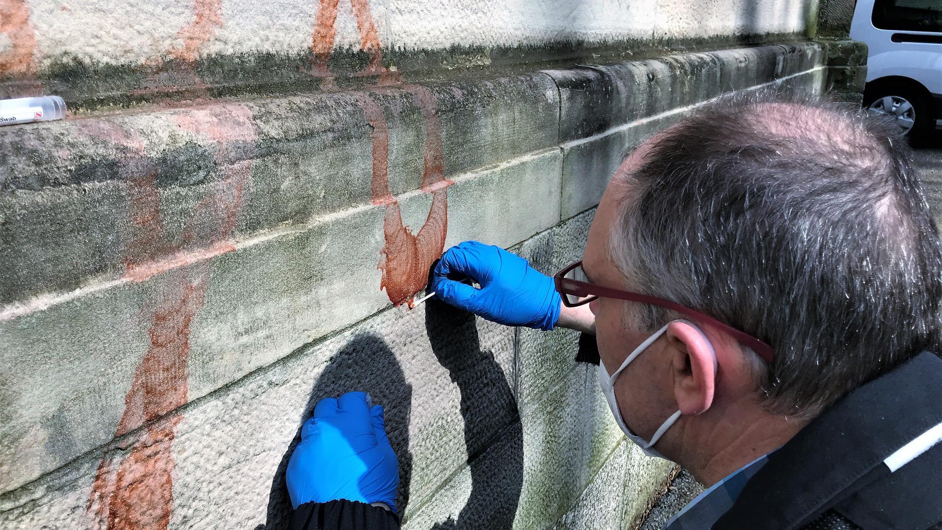 Ein Mann tupft mit einem Wattestäbchen Farbe von einer Schmiererei an einer Kirchenwand.
