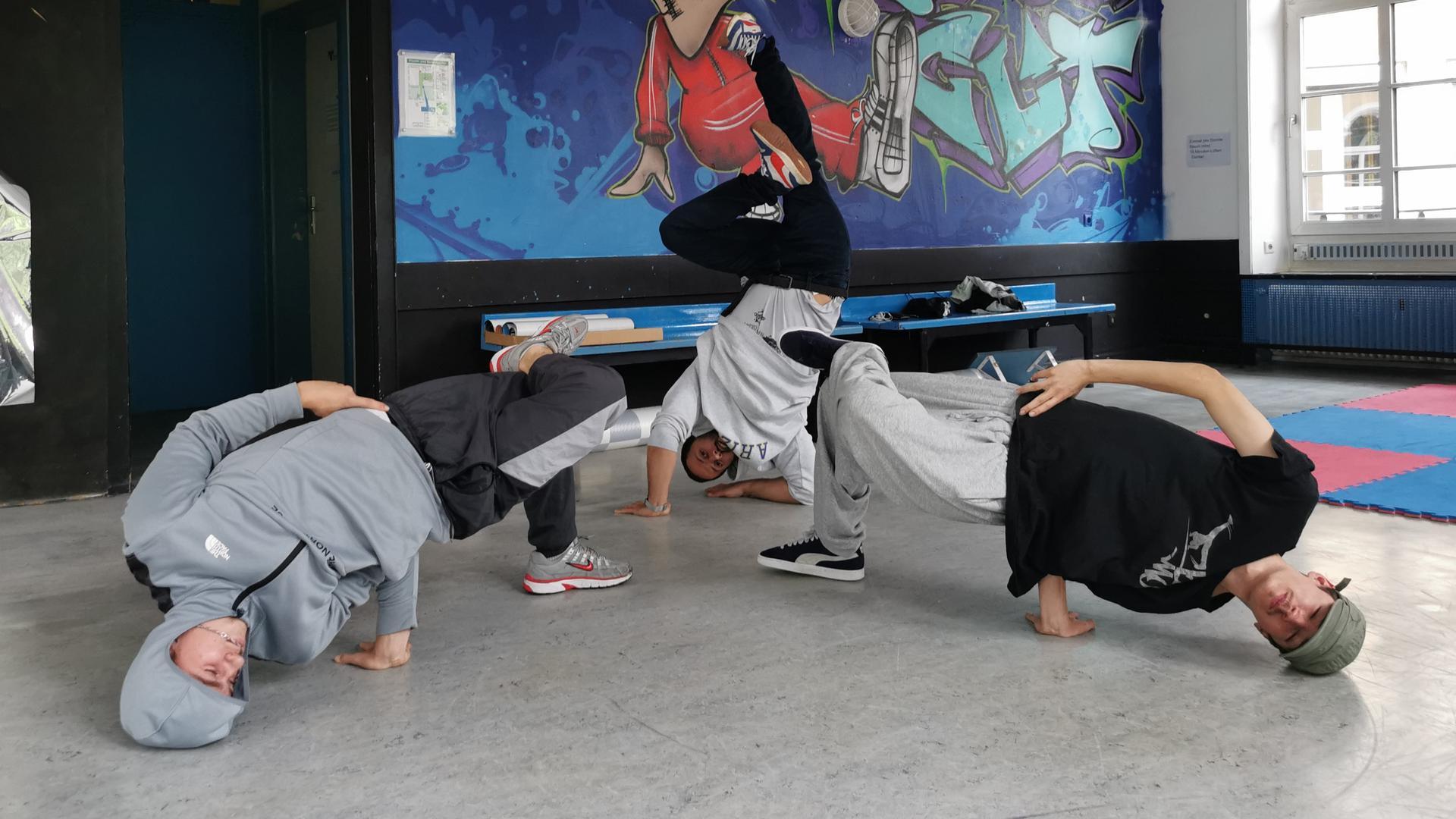 Drei Breakdancer machen eine akrobatische Figur vor einer Graffiti-Wand.