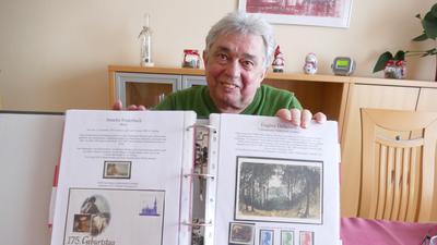 Ein Mann zeigt ein Briefmarkenalbum.