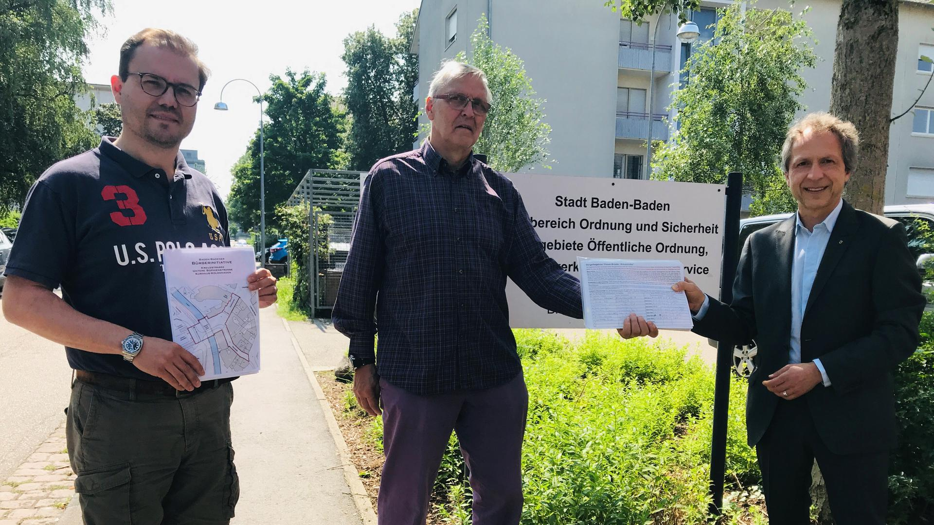 """Thomas Meurer (von links) und Michael Greising von der Bürgerinitiative """"Fußgängerzone Kreuzstraße/Fieser-Brücke"""" übergeben Bürgermeister Roland Kaiser weitere Listen mit Unterschriftenlisten."""