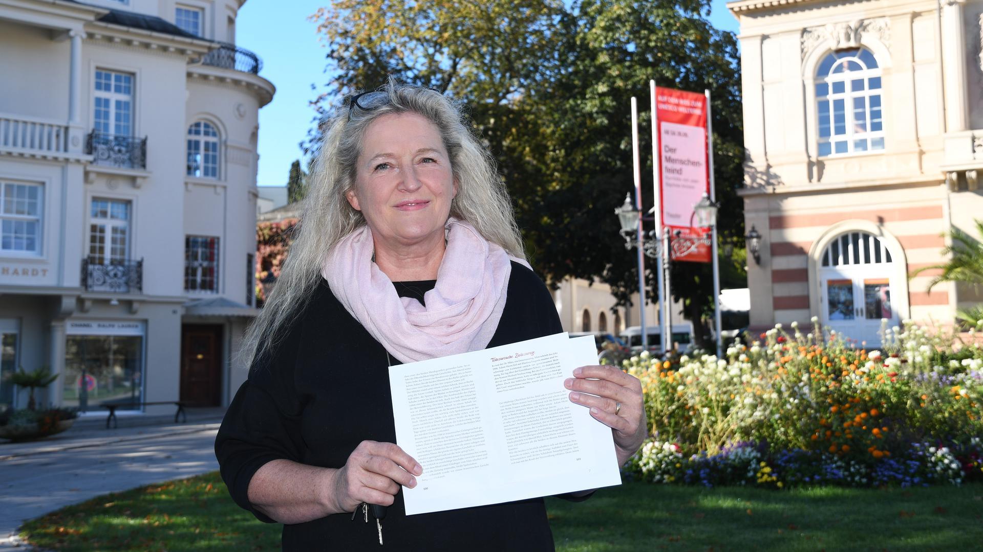 Die Buchautorin Christiane Krause-Dimmock hält die ersten Seiten ihres neuen Buches hoch.