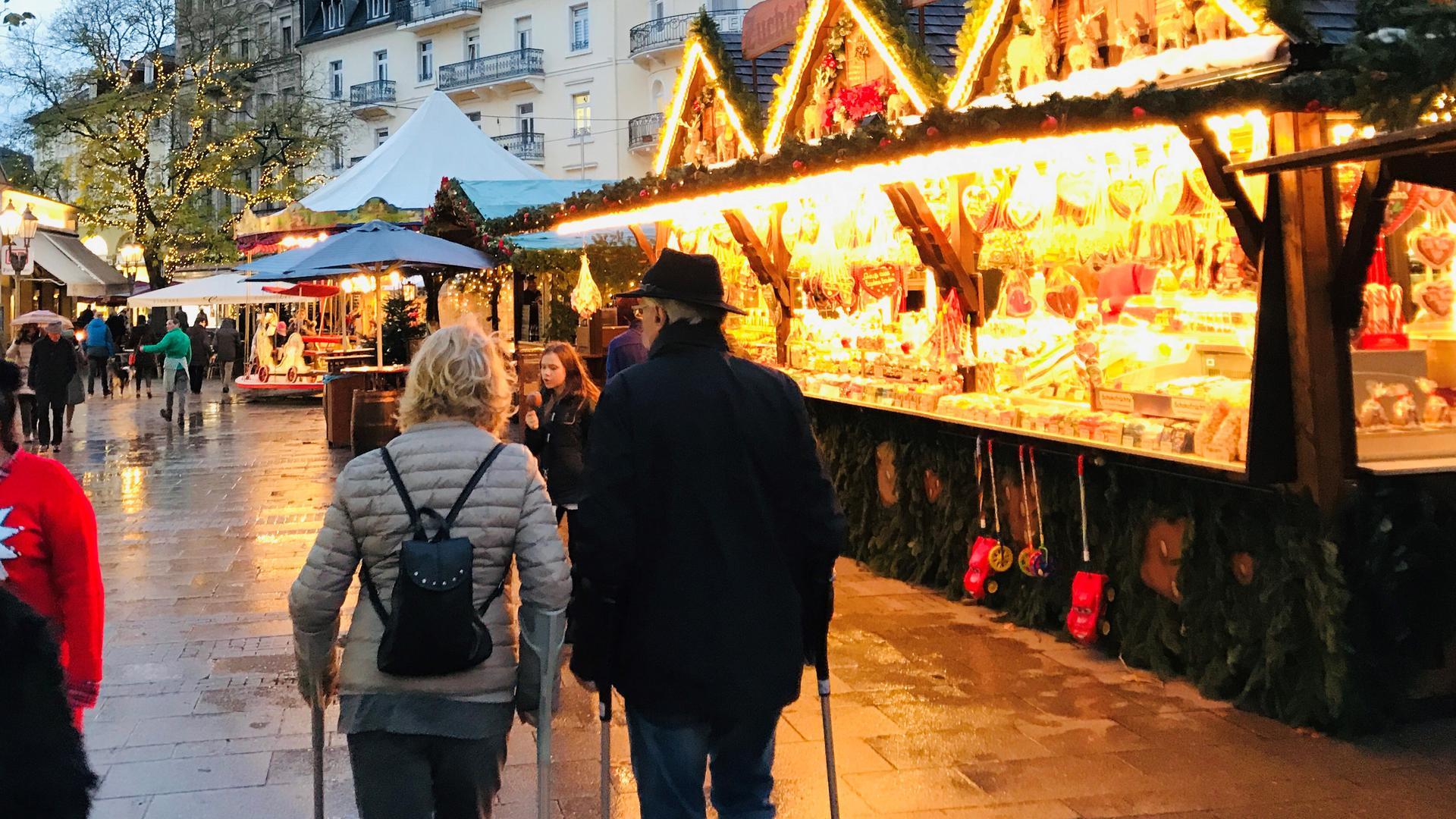 Passanten flanieren auf der Fieser-Brücke in Baden-Baden an Ständen des Christkindelsmarktes vorbei.