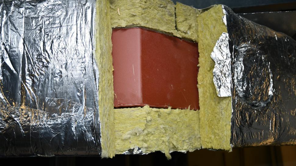 Ein Stahlträger ist mit Stahlwolle umkleidet. An einer Stelle fehlt die Isolierung.